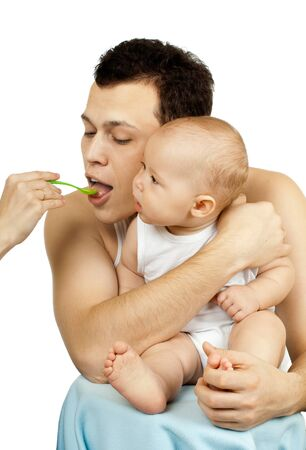 dad with  little baby, child eat of spoon, on white background, isolated photo