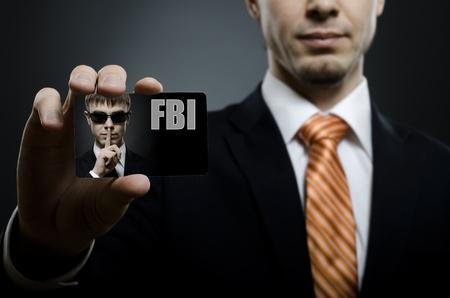 agente: agente segreto in costume cravatta nera e arancio raggiungere sulla macchina fotografica e mostrare biglietto da visita, close up Archivio Fotografico