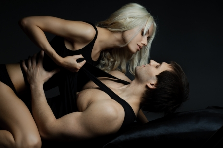 passionate lovers: muscular handsome sexy guy with pretty woman, on dark background, glamour  light