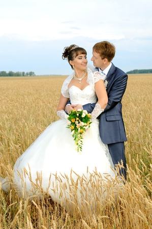 cutie happy married  couple  on nature, on wheaten field,  embrace and smile photo