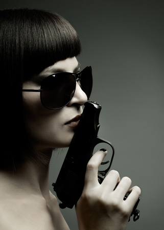 sensuality  beautifull  girl, close face , with pistol, on dark background, glamour light photo