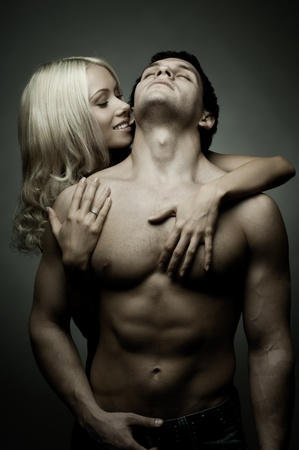 vehement: muscular handsome sexy guy with pretty woman, on dark background, glamour light Stock Photo
