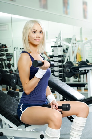 happy cutie athletic girl ,  exercise with dumbbells and smile, in  sport-hall Stock Photo - 13589947