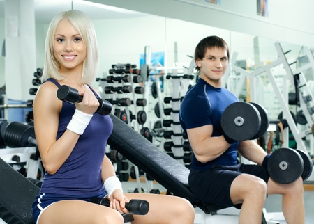 cutie: happy cutie athletic girl and guy,  exercise with dumbbells and smile, in  sport-hall