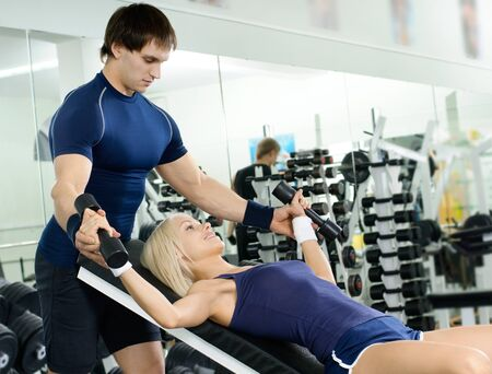 brawny: happy cutie athletic girl and guy,  exercise with dumbbells and smile, in  sport-hall