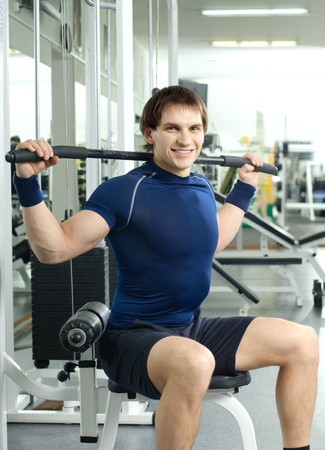 cutie: happy cutie athletic guy ,  execute exercise on sport-apparatus, in  sport-hall, look on camera and smile Stock Photo