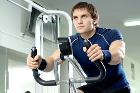 vigorous: beautifull strong athletic guy,  execute exercise on exercise-bicycle, in  sport-hall