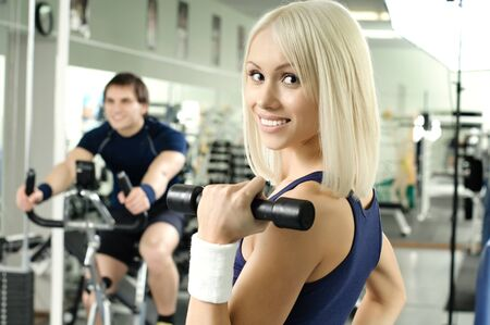 happy cutie athletic girl ,  exercise with dumbbells and smile, in  sport-hall photo