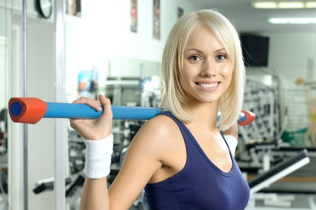 happy cutie athletic girl ,  execute exercise on sport-apparatus  and smile, in  sport-hall Stock Photo - 13589993