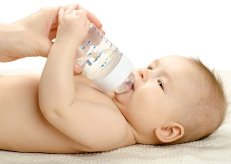 the very  beautiful  little baby drink of  bottle, lie on white background, isolated photo