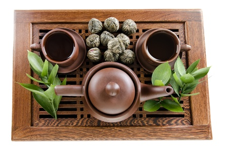 still life of the clay teapot and  cup on wooden trivet,  on white background, isolated photo