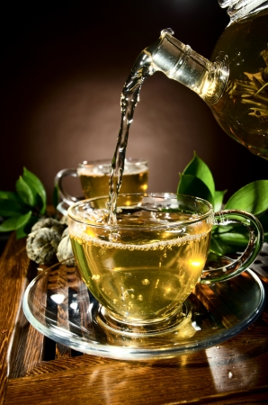 brown cup tea: vertical photo, of the glass teapot flow green tea in cup on brown background,  tea ceremony Stock Photo