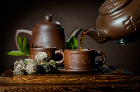 horizontal photo, of the clay teapot tea flow in  cup on brown background,  tea ceremony photo