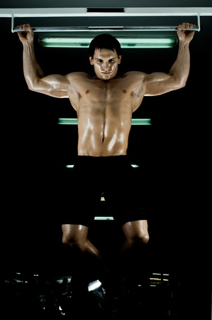 very power athletic guy ,  execute exercise tightening  on horizontal bar, in  sport-hall, glamour light Stock Photo - 14160437