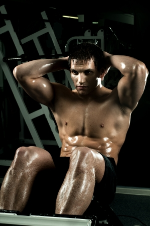 very power athletic guy ,  execute exercise on muscles belly, in  dark sport-hall photo