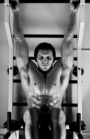 very power athletic guy ,  execute exercise tightening  on horizontal bar, in  sport-hall, hard light Stock Photo - 14160663