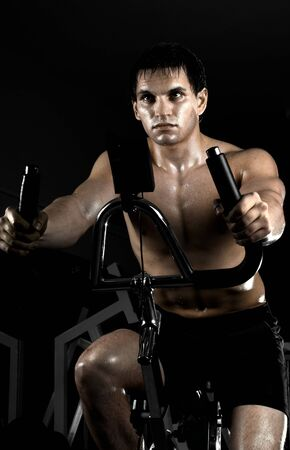 apparatus: beautifull strong athletic guy,  execute exercise on exercise-bicycle, in  dark sport-hall