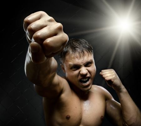 plucky: horizontal photo  muscular young  guy street-fighter, cuff  fist close up on camera and yell , hard light