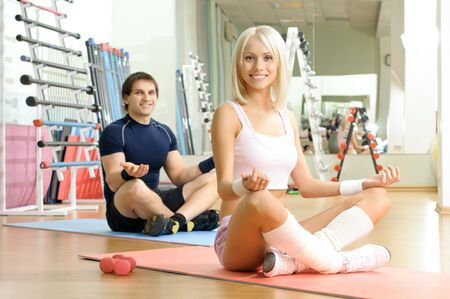 happy cutie athletic girl and guy,  execute exercise  and smile, in  sport-hall photo