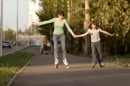 Mother with the daughter go on  roller skates, outdoor, in the evening summer photo