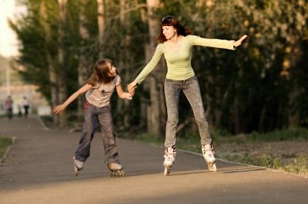 niño en patines: Madre con la hija van en patines, al aire libre, en la noche de verano