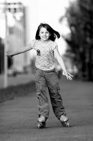 little young girl go on  roller skates, outdoor, black-and-white photography Stock Photo - 14549694