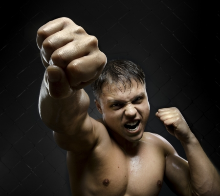 horizontal photo  muscular young  guy street-fighter, cuff  fist close up on camera and yell , hard light Stock Photo - 14549685