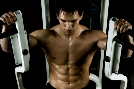 physical training: very power athletic guy ,  execute exercise with  weight, in  sport-hall, beauty glamour light