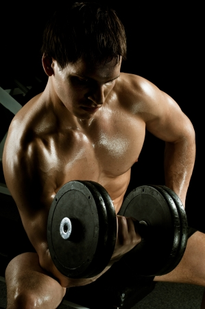 very power athletic guy ,  execute exercise with  dumbbells, in  sport-hall, beauty glamour light Stock Photo - 14549695