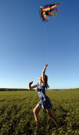 quickly: The young girl quickly runs on a green glade with kite,  happy smiles