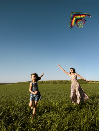The young girl with  mother quickly runs on a green glade ,  fly a kite and happy smiles photo