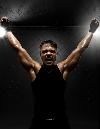 vertrical photo  muscular young  guy street-fighter,  triumphant cries  yell , hard light Stock Photo - 14549687
