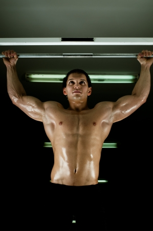 very power athletic guy ,  execute exercise tightening  on horizontal bar, in  sport-hall, glamour light Stock Photo - 14571070