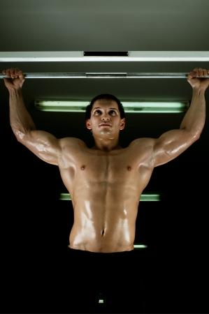 vigorous: very power athletic guy ,  execute exercise tightening  on horizontal bar, in  sport-hall, glamour light Stock Photo