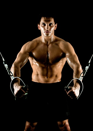 very power athletic guy ,  execute exercise on  on sport-apparatus, on black background Stock Photo - 14571069
