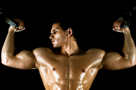 vigorously: very power athletic guy ,  execute exercise on  on sport-apparatus, on black background
