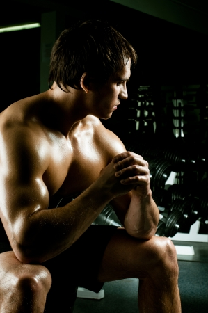 very power athletic guy rest  after execute exercise, in dark  sport-hall photo