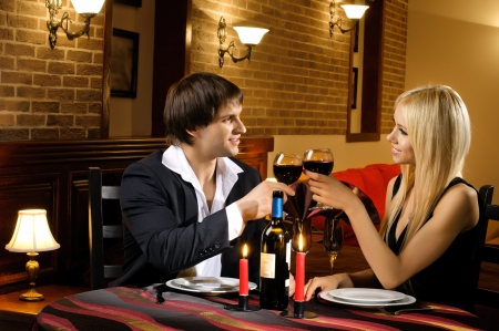 romantic evening with wine: romantic evening date in hotel room, or supper in restaurant, happy couple with wine glass