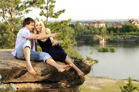 aloft: romantic  date on nature, happy couple sit aloft on rock  with beautiful view