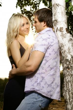 cordially: romantic evening date on nature, couple  embrace on beautiful sunset   Stock Photo