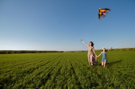 papalote: La niña con la madre se queda rápidamente en un claro verde, volar una cometa y sonríe feliz