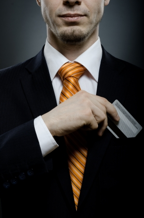 put up: businessman in black costume and orange necktie put or take out credit card in pocket, close up Stock Photo