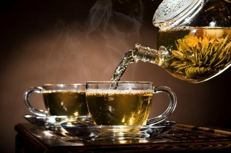pellucid: foto horizontal, del t� de vidrio verde en el flujo de la tetera taza de caf� en el fondo, la ceremonia del t�