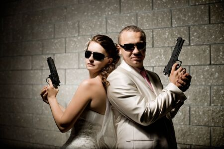 newly married couple in white wedding dress, with black pistols photo