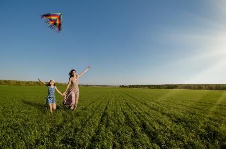papalote: La ni�a con la madre se queda r�pidamente en un claro verde, volar una cometa y sonr�e feliz