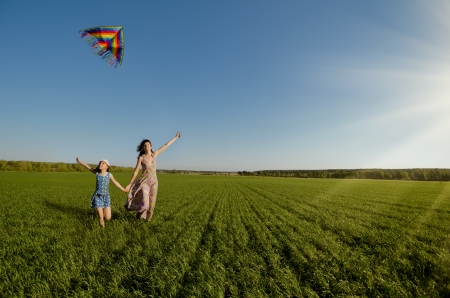 The young girl with  mother quickly runs on a green glade ,  fly a kite and happy smiles