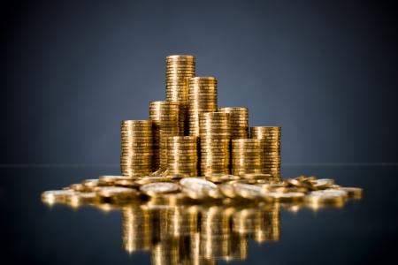 mucho dinero: todavía la vida de muchísimos monetaria rouleau oro o moneda de cambio, sobre fondo azul oscuro Foto de archivo