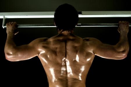 very power back athletic guy ,  execute exercise tightening  on horizontal bar Stock Photo - 14609094