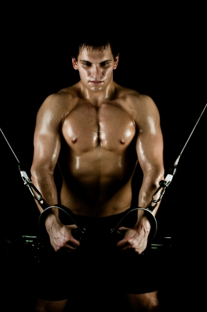 Endurance: very power athletic guy ,  execute exercise on  on sport-apparatus, on black background