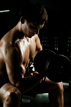 vigorous: very power athletic guy ,  execute exercise with  weight, in  dark sport-hall Stock Photo